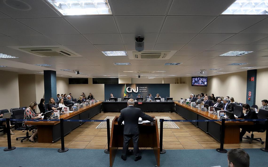 Visão de sessão do Conselho Nacional de Justiça, o CNJ. Conselheiros sentados ao longo de mesa que forma três lados de um quadrado. Em pé ao púlpito no centro, um homem fala aos conselheiros. Atrás na parede, o letreiro escrito