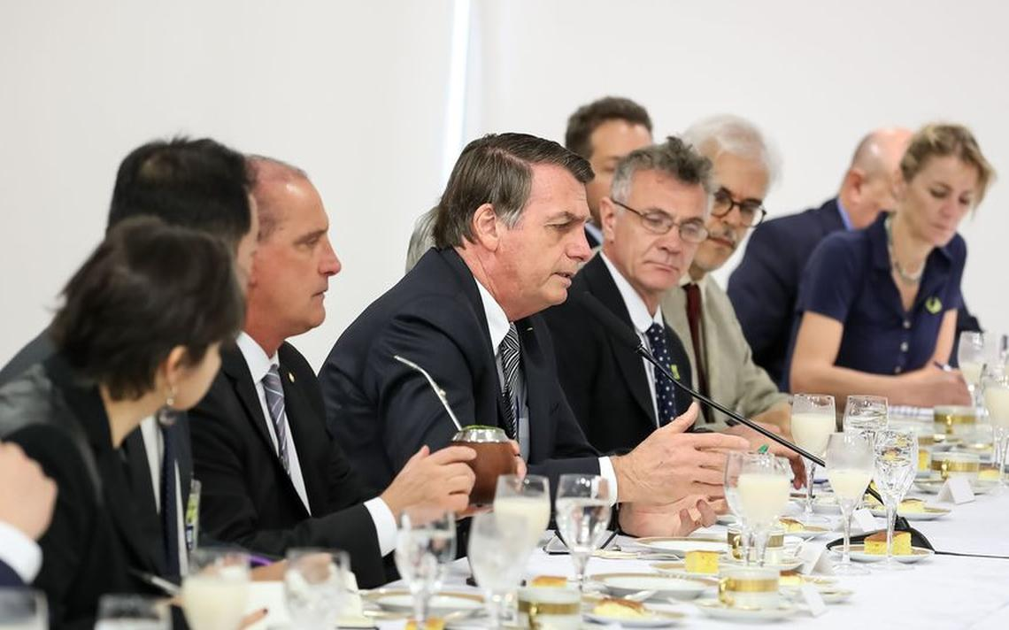 Mesa com café da manhã servido. Estão sentados o presidente, os ministros Onyx e Heleno e jornalistas estrangeiros. Bolsonaro está falando e os demais olham em sua direção.