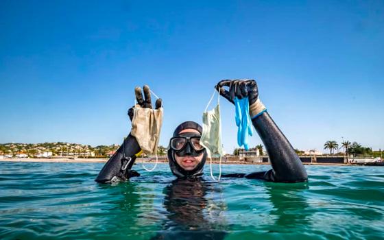 Mergulhador com trajes de mergulho segura três máscaras recolhidas do mar. Só a cabeça e braços estão fora da água