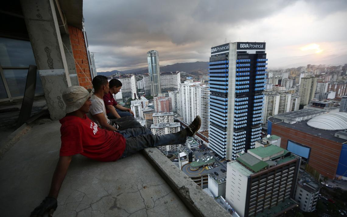 Três homens sentados em um andar alto de um prédio em construção. Eles observam o horizonte repleto de prédios, com céu nublado.