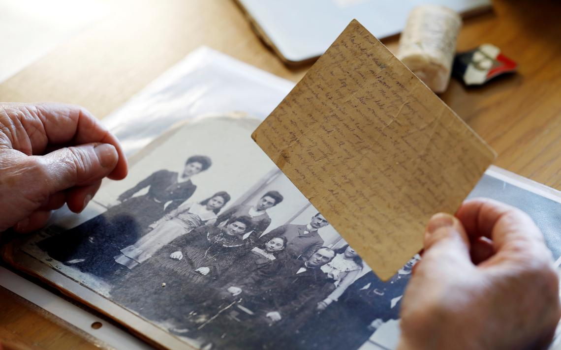 Mãos de uma senhora seguram uma pequena carta e se apoiam em um álbum com uma foto antiga de família.