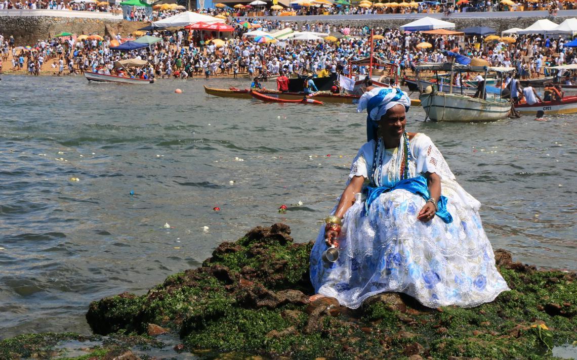 Mulher do candomblé se apoia em rochas na praia, durante celebração do Dia de Iemanjá