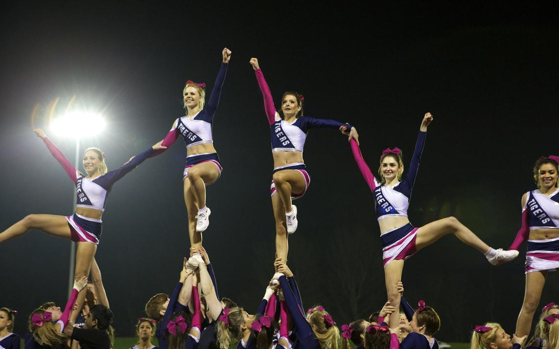 Cinco cheerleaders são levantadas por outras e fazem pose durante apresentação.
