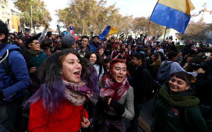 Manifestação de estudantes. Na frente, três mulheres jovens.