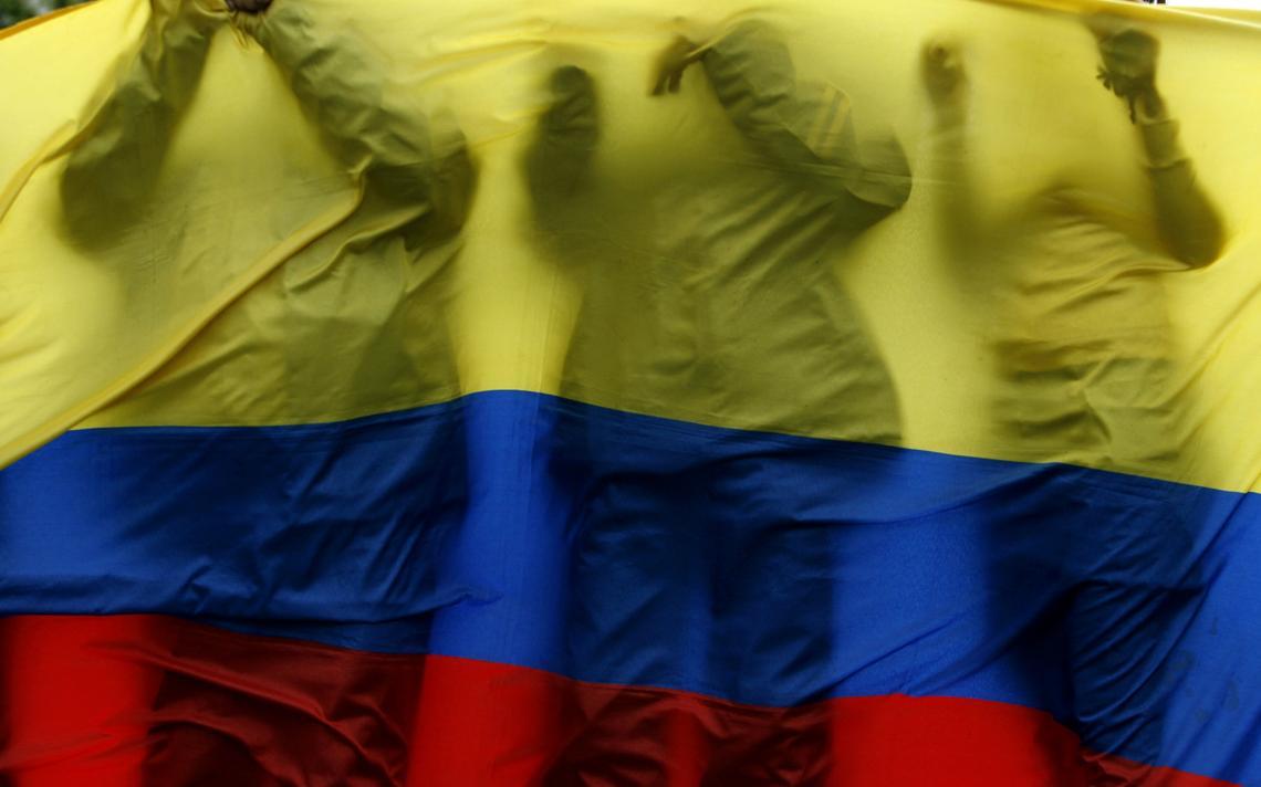 Bandeira da Colômbia. Atrás, a silhueta de três pessoas encostadas na bandeira.