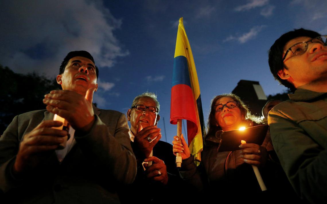Quatro pessoas seguram velas. Uma delas também segura a bandeira da Colômbia.