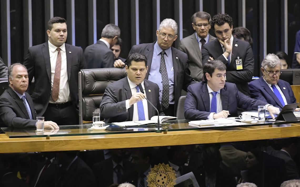 Sentado ao centro da mesa no plenário, Alcolumbre segura com a mão direita o microfone à sua frente. Sentado ao seu lado e em pé ao seu redor, outros políticos e consultores legislativos observam a sessão.