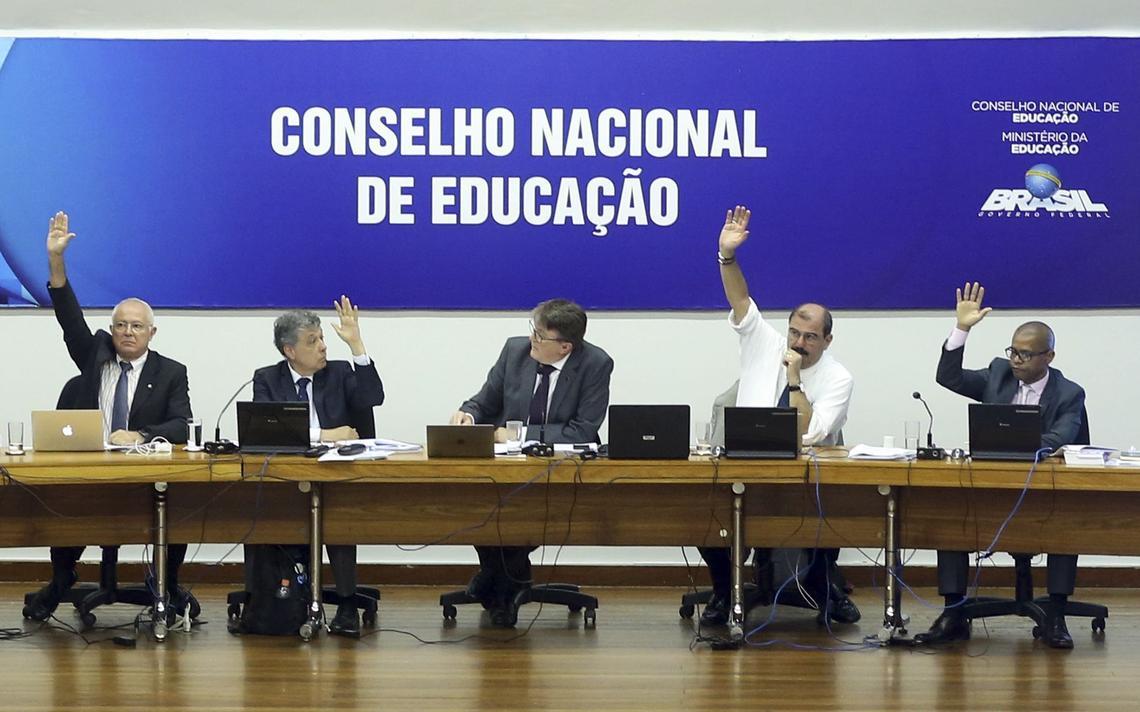 Sentados à mesa, conselheiros levantam a mão em votação. Atrás, mural com os dizeres