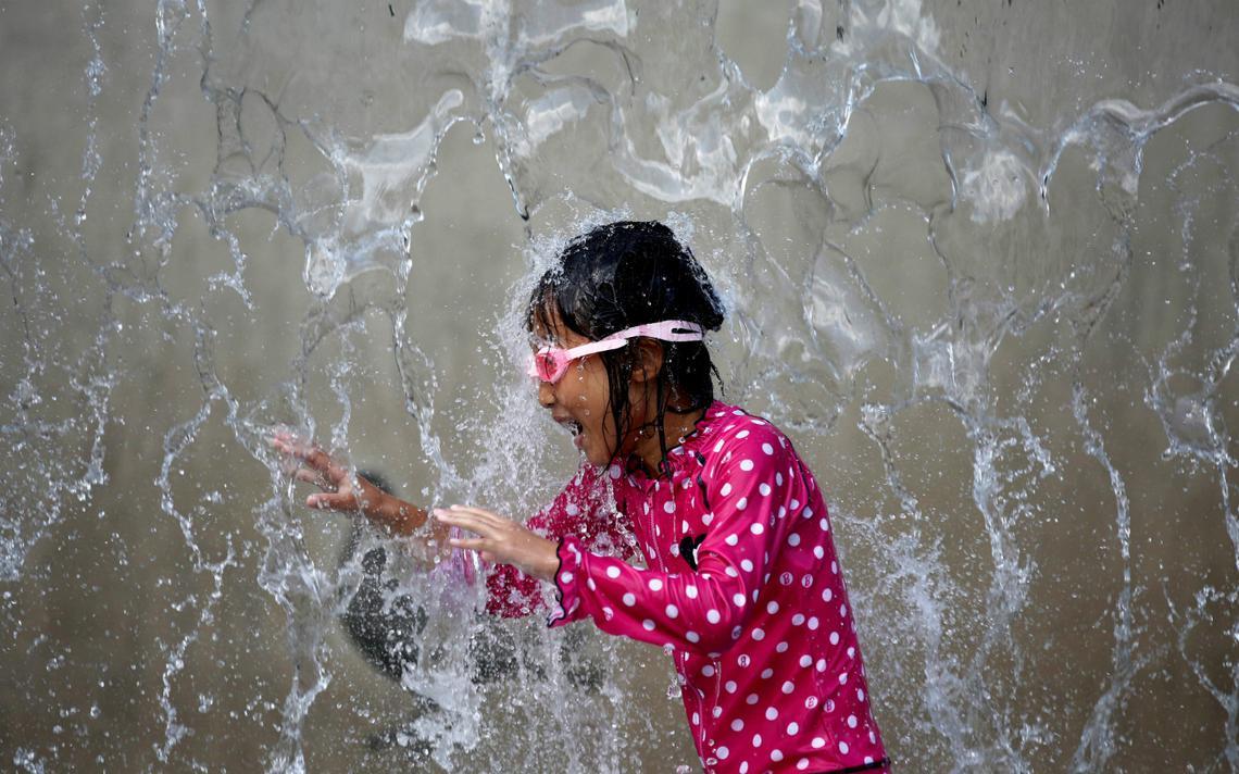 Criança brinca e se refresca em fonte em Tóquio, no Japão