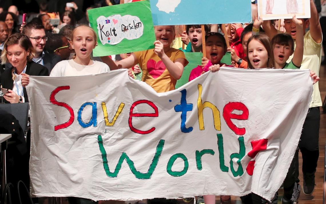 Crianças seguram faixa dizendo