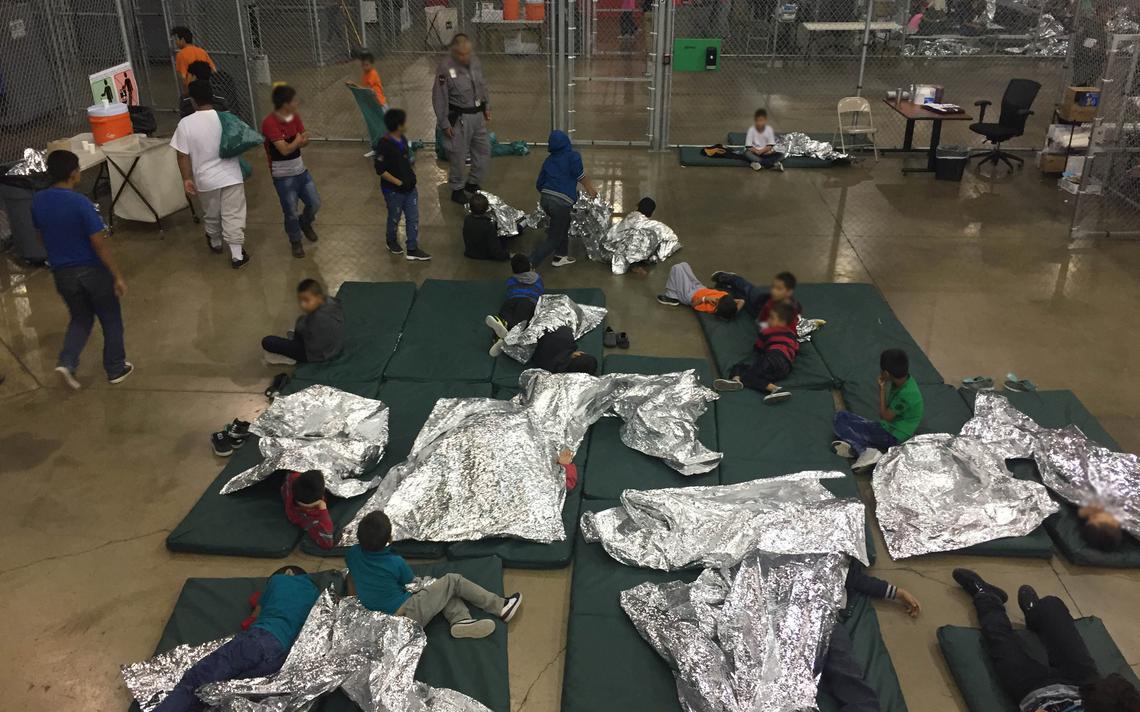 Colchões jogados sobre o chão, com crianças deitadas usando papel alumínio como cobertor. O local tem uma grade metálica em volta.