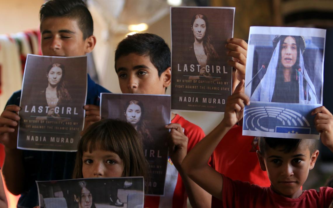Crianças yazidi seguram imagens de Murad e da capa de seu livro no Iraque