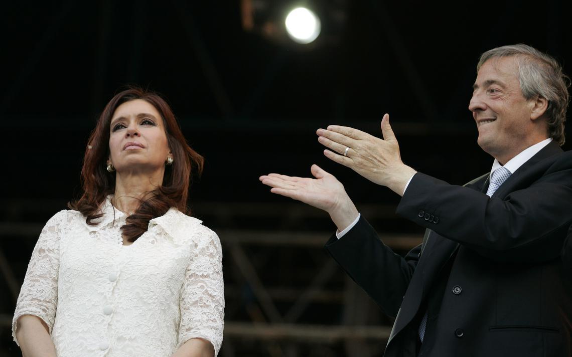 Com expressão séria, Cristina olha para frente, na Casa Rosada. Ao lado dela, Néstor sorri e aponta com os dois braços para a nova presidente.
