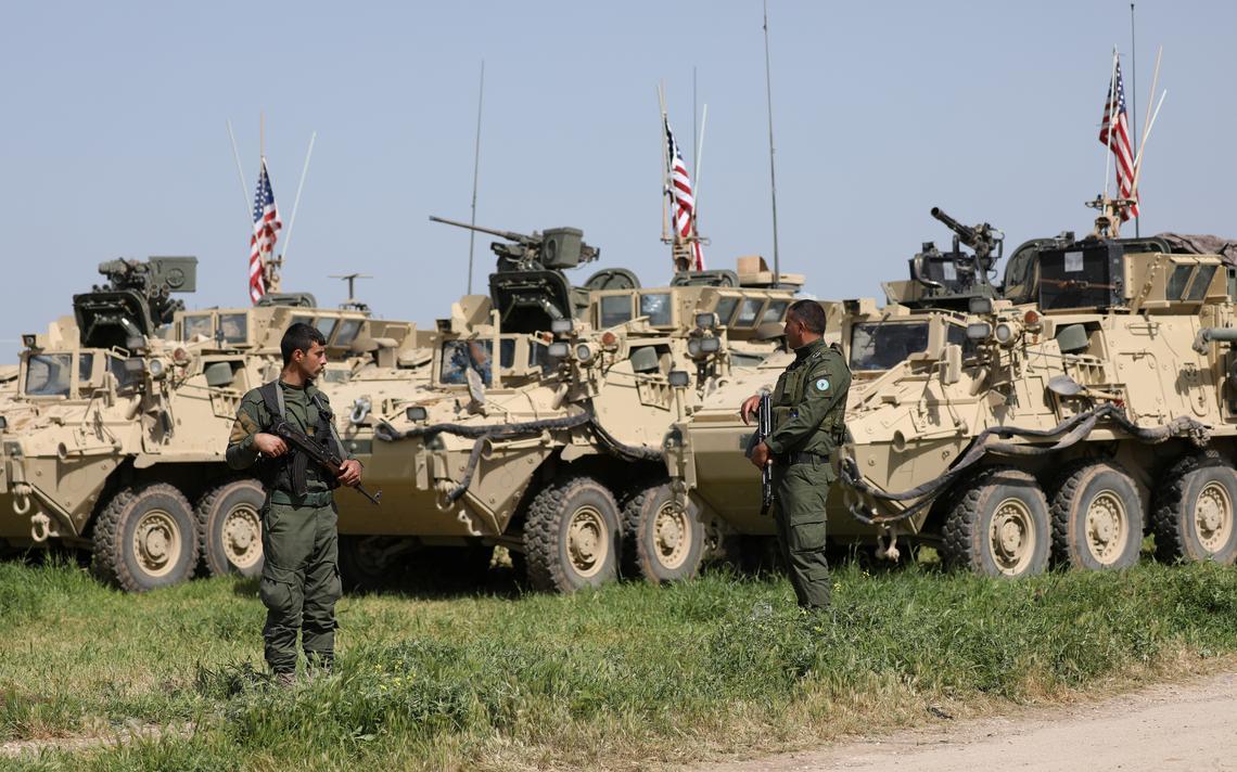 Dois homens curdos fardados, com armas na mão, estão de pé e olham ao redor. Ao lado, veículos militares americanos, com bandeiras dos EUA. Estão em campo aberto, duranteo o dia.