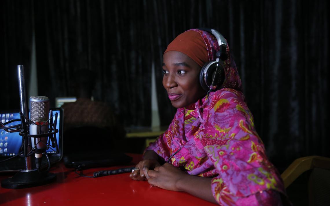 Sentada, apresentadora usa fones de ouvido e tem um microfone na bancada à sua frente.