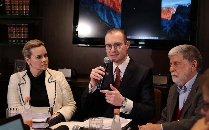 Os três estão sentados lado a lado à mesa. Microfones e documentos sobre a mesa. Atrás, monitor grande e livros.