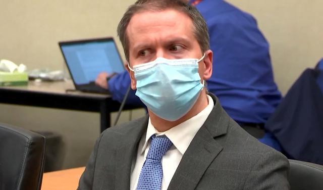 Homem branco com cabelo curto moreno claro usa terno e uma máscara cirúrgica está sentado, olhando para o lado sem mover a cabeça