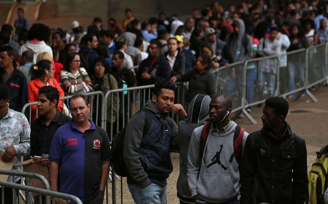 Pessoas fazem fila por oportunidade de emprego no centro de São Paulo. No principal plano da imagem, há 4 homens encostados em uma grade. O da esquerda é branco e os outros são negros. Ao fundo, há uma multidão em uma fila aparentemente desorganizada.