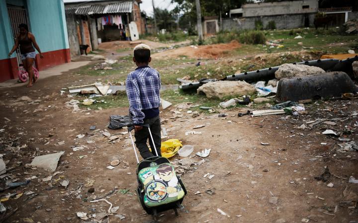 Garoto com material escolar em comunidade do Rio, em 2016