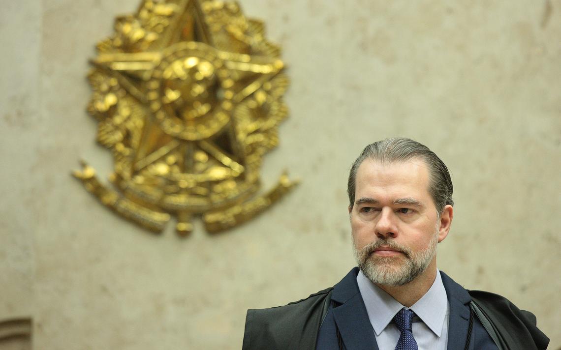 Sentado e vestindo capa dos magistrados do Supremo, Toffoli observa sessão no plenário. Atrás dele, parede com emblema do brasão da República.