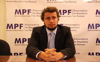 Imagem mostra procurador sentado à mesa, de terno e gravata azul clara, com as mãos cruzadas, olhando para seu canto esquerdo