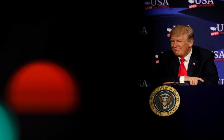 Donald Trump no canto da imagem, sentado à mesa de um evento. O resto da foto está no escuro.