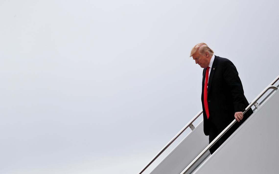 Trump é visto de lado, descendo sozinho a escada do avião. A foto captura apenas Trump, a escada e o céu nublado.