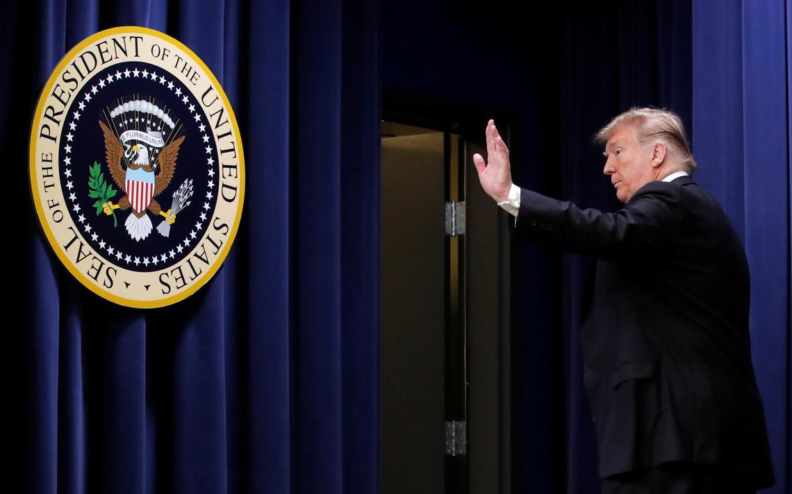 De lado e caminhando para uma porta lateral, Trump acena com a mão. Próximo a ele, o brasão da Presidência dos EUA fixado na parede.
