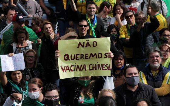 """Em meio a um grupo, um manifestante levanta uma placa com a frase """"não queremos a vacina chinesa"""""""