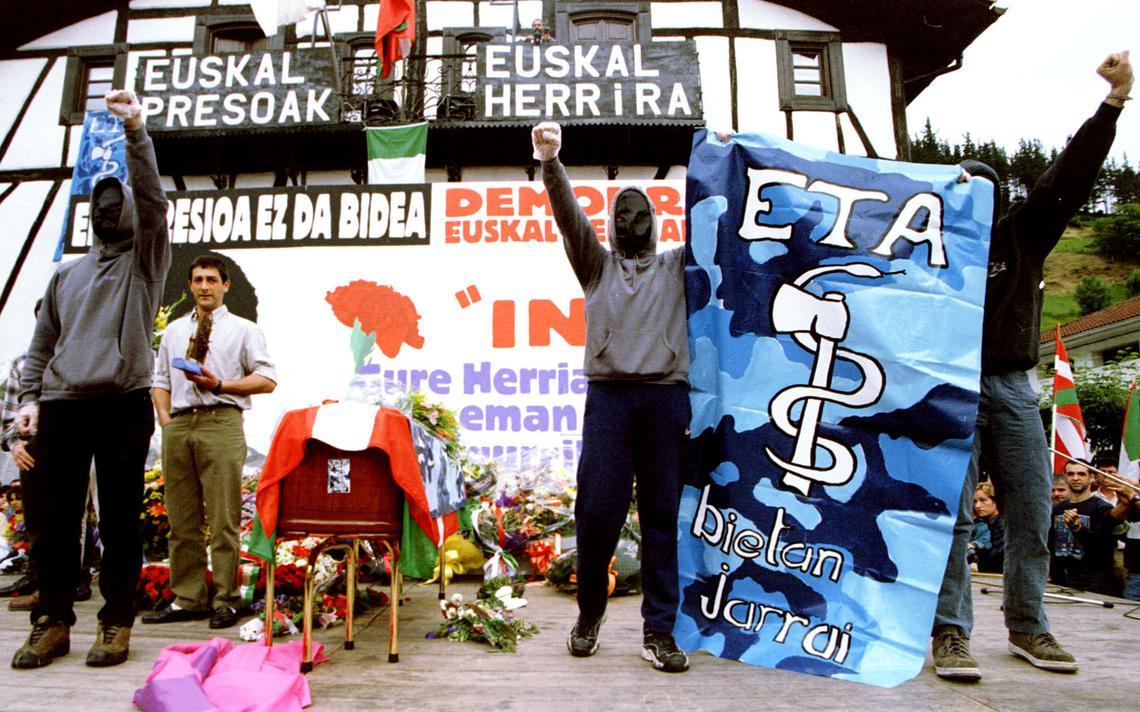 Três pessoas, com o rosto coberto, erguem os punhos com cartazes de apoio ao ETA.