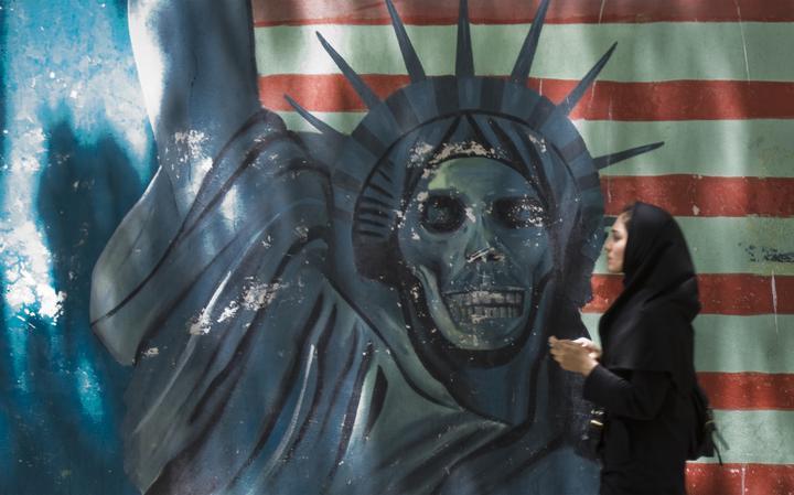 No muro, está pintada a estátua da liberdade com uma caveira no lugar da cabeça. Atrás da estátua, a bandeira dos Estados Unidos. De perfil, uma mulher vestida de preto e com véu passa em frente ao muro.