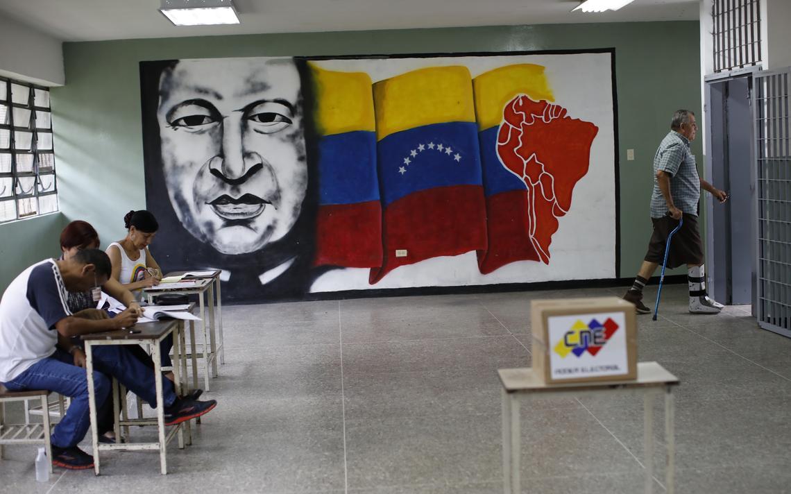 Seção eleitoral com apenas um eleitor. Na sala, há mesários, uma urna e também um mural com a imagem de Hugo Chávez e da bandeira da Venezuela.