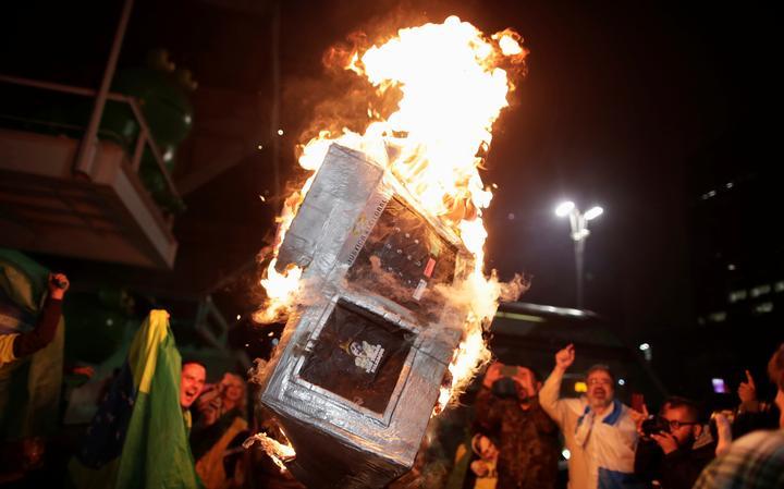 Pessoas em volta de uma caixa em chamas. A caixa representa a urna eletrônica.
