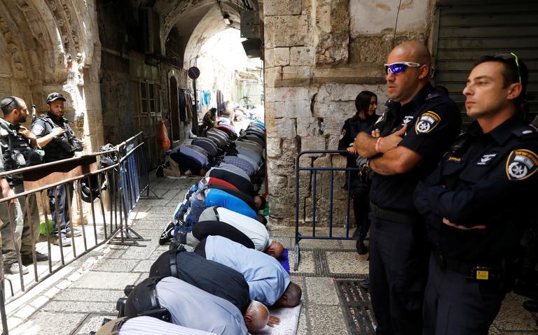 Dois policias israelenses de pé e braços cruzados. Muçulmanos rezam ajoelhados na frente dos guardas.