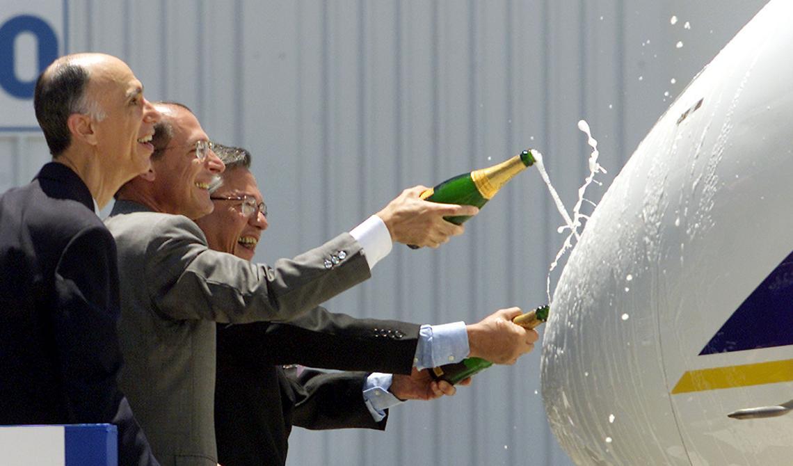 Dois políticos tucanos e o presidente da Embraer sorriem e jogam espumante em uma aeronave da empresa.