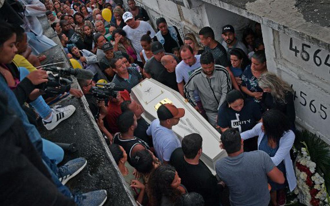 Em corredor dentro do cemitério, pessoas carregam caixão.