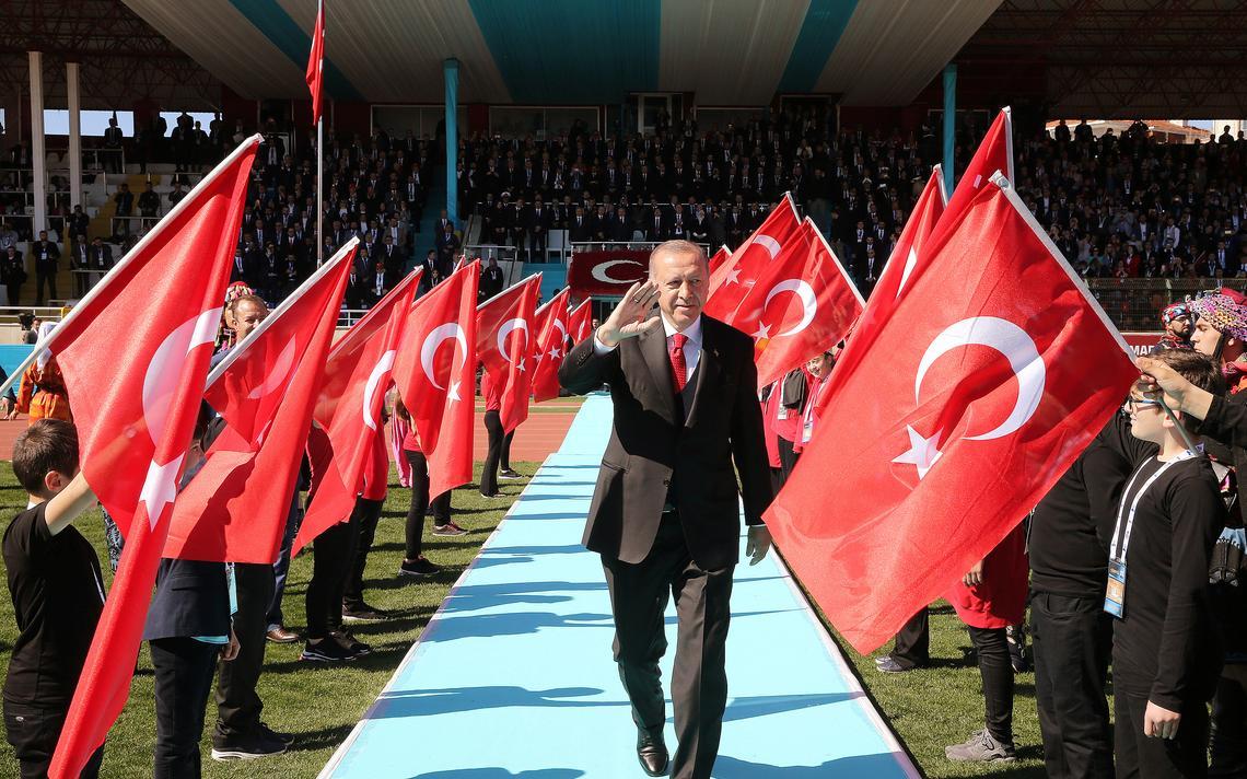Erdogan anda em corredor em que dezenas de crianças empunham bandeiras da Turquia. Atrás, uma arquibancada lotada.