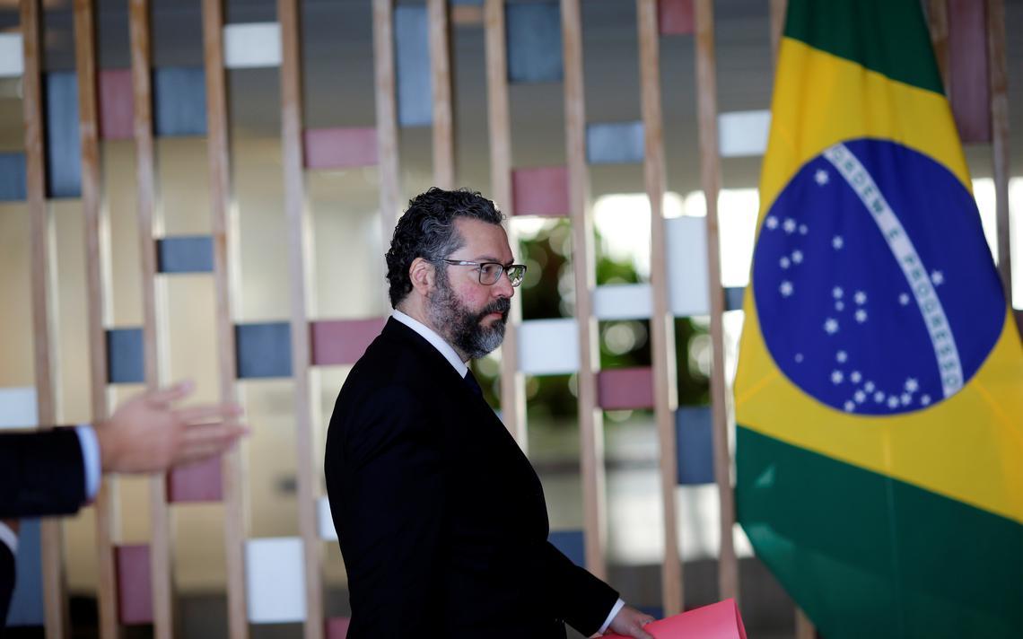 Segurando uma pasta, Ernesto Araújo está de pé em salão do Itamaraty e ao lado de uma bandeira do Brasil.