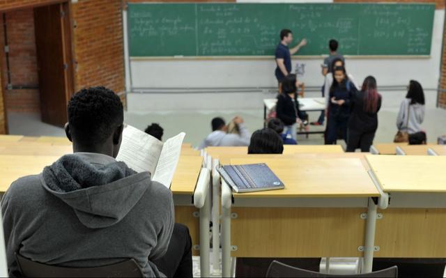 Estudante negro, de costas, está sentado à carteira em uma sala de aula. Mais longe, outros estudantes estão em pé, conversando.