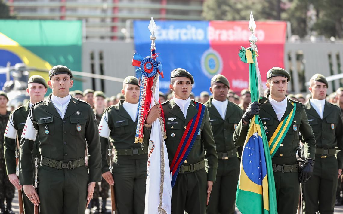 Militares fardados e enfileirados em pátio ao ar livre, durante cerimônia.