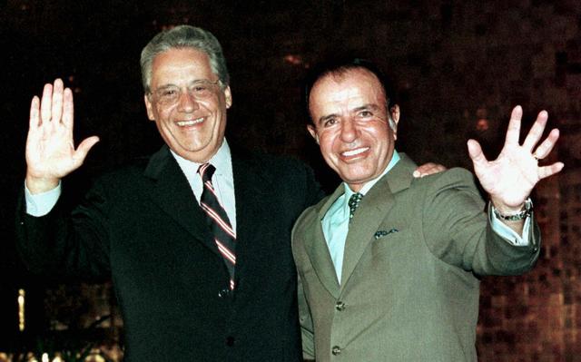 Fernando Henrique Cardoso e Carlos Menem se abraçam em reunião em Brasília em 1999. Eles se abraçam com um braço e acenam com o outro para a câmera.