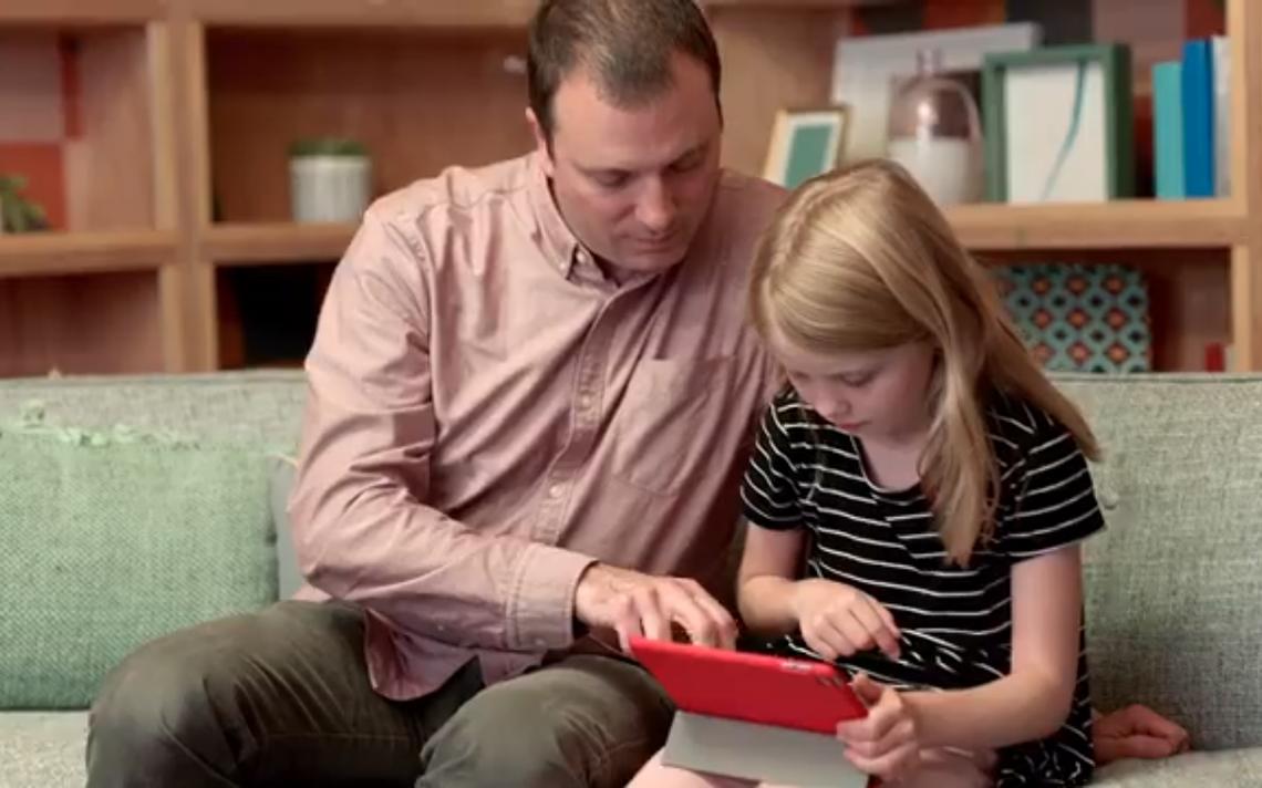 Imagem de homem ajudando criança a usar aplicativo usada na divulgação do 'Messenger para crianças'