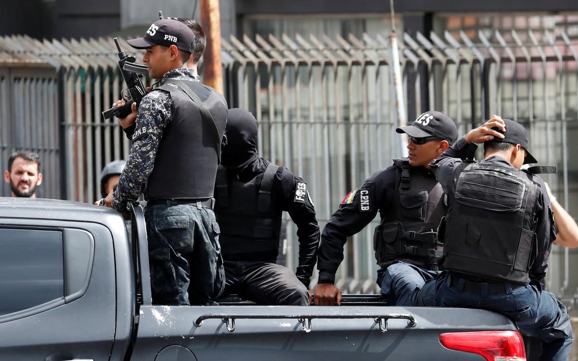 Cinco policiais armados em cima de uma caminhonete passam por uma rua. Um deles está com o rosto coberto. Um pedestre venezuelano observa a viatura.