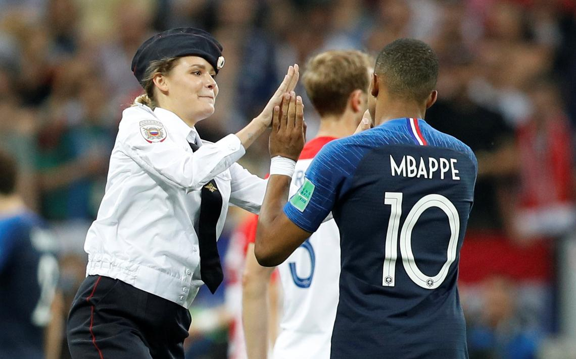 Vestida de policial, manifestante bate as mãos com o jogador francês.