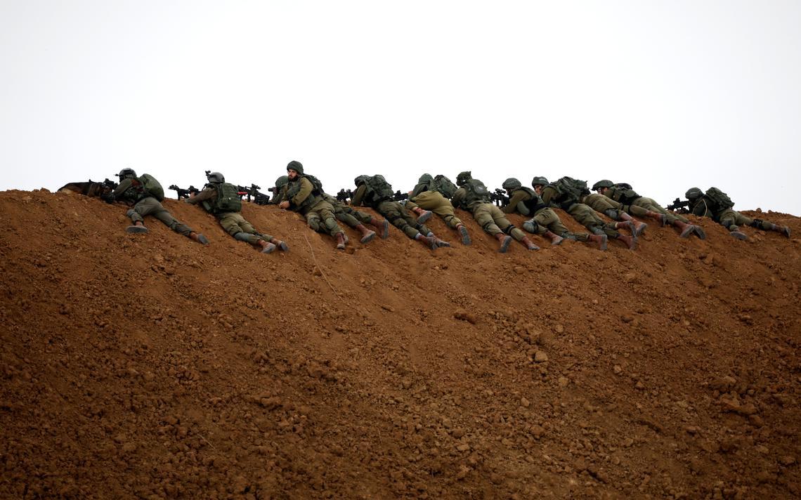 12 soldados, com trajes e armas de combate, esgueirados em um um pequeno monte de terra.