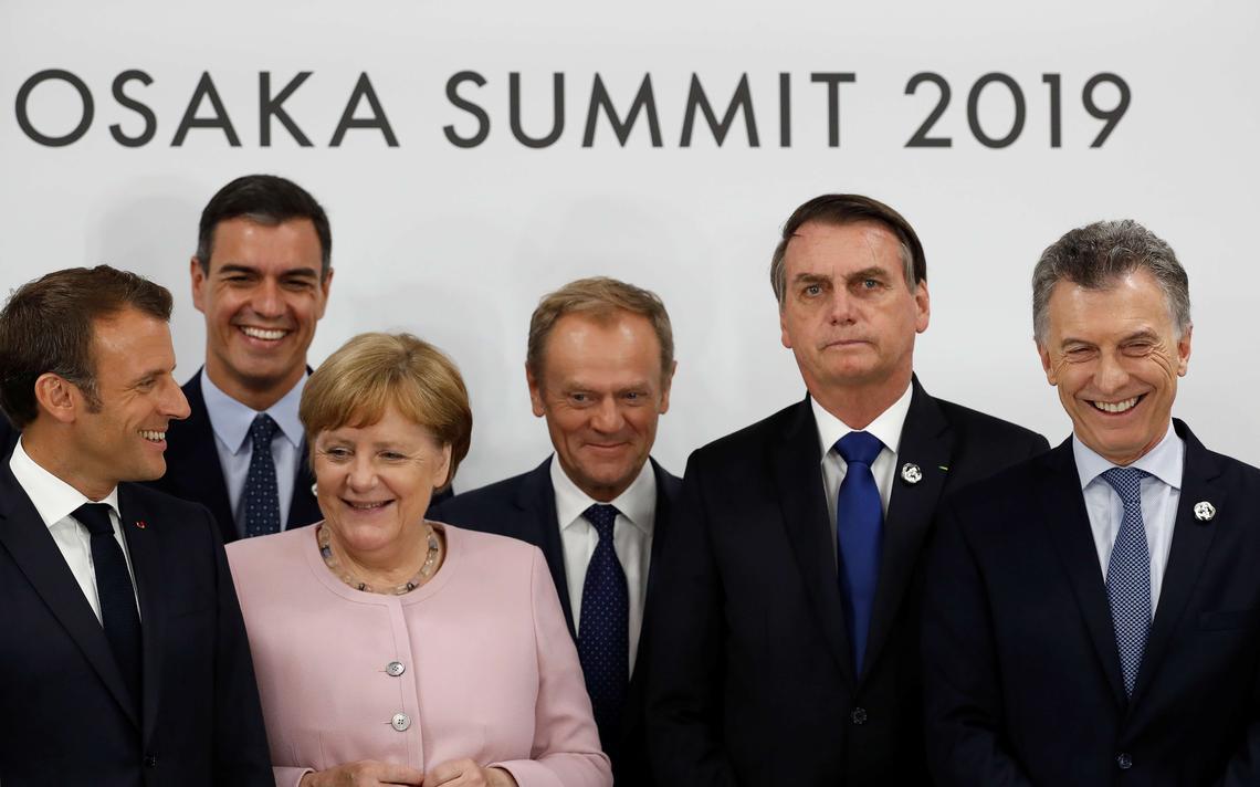 Lado a lado da esquerda para a direita: Emmanuel Macron, Pedro Sánchez, Angela Merkel, Donald Tusk, Jair Bolsonaro e Mauricio Macri. Atrás, painel com os dizeres em inglês