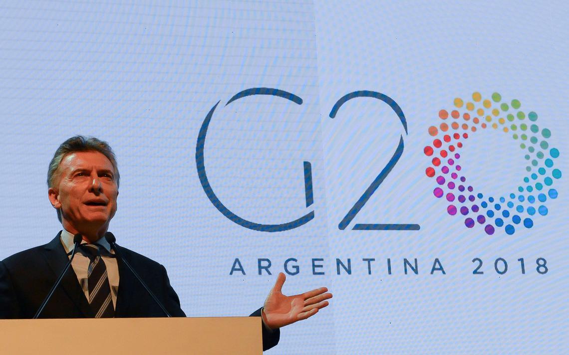 Macri fala e gesticula em púlpito. Atrás, painel com os dizeres