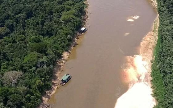 Vista aérea de dois barcos com dragas fazendo garimpo ilegal em rio no meio da Amazônia