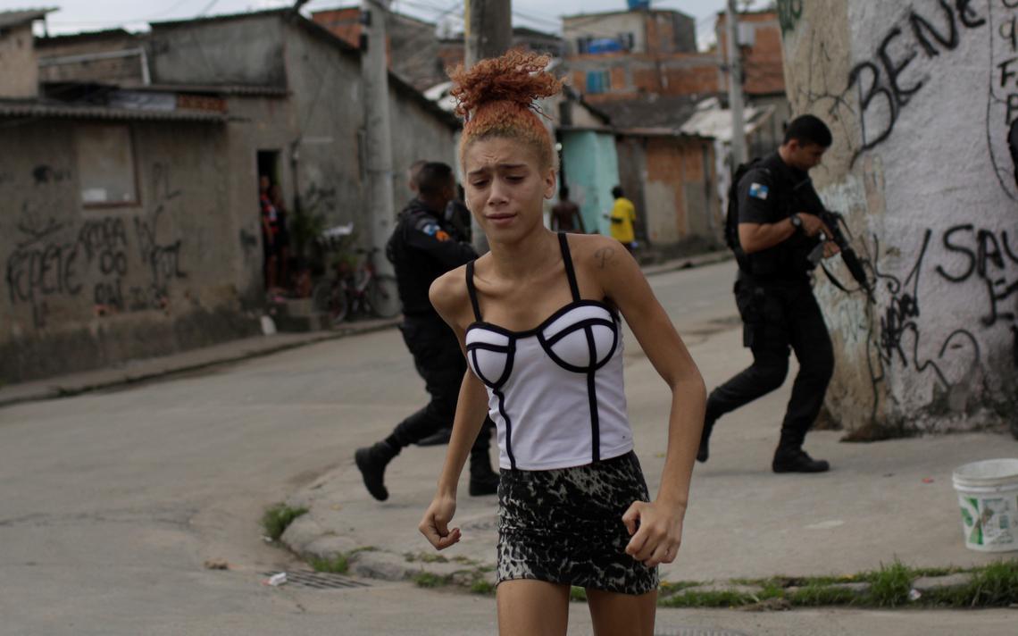 Garota corre durante ação de policiais na comunidade Cidade de Deus, em março de 2018 no Rio