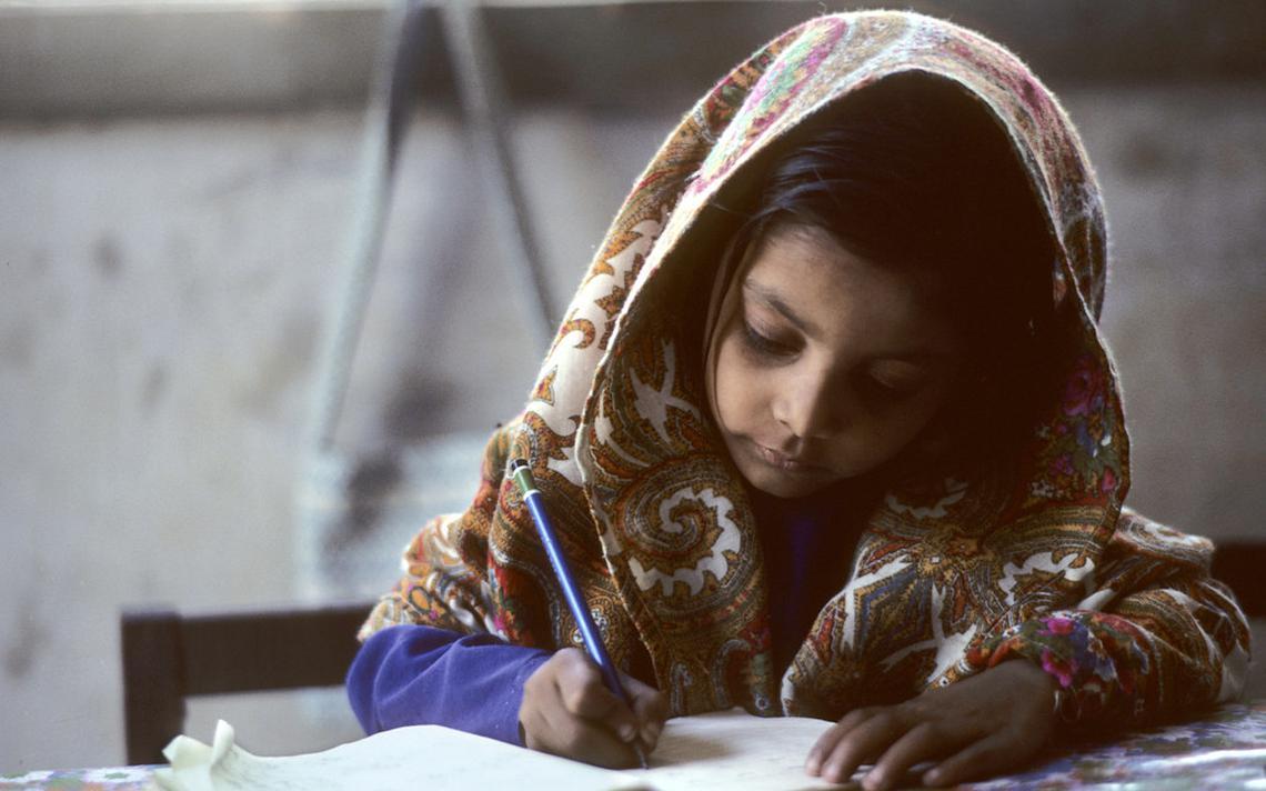Garota paquistanesa faz lição de casa na cidade de Karachi